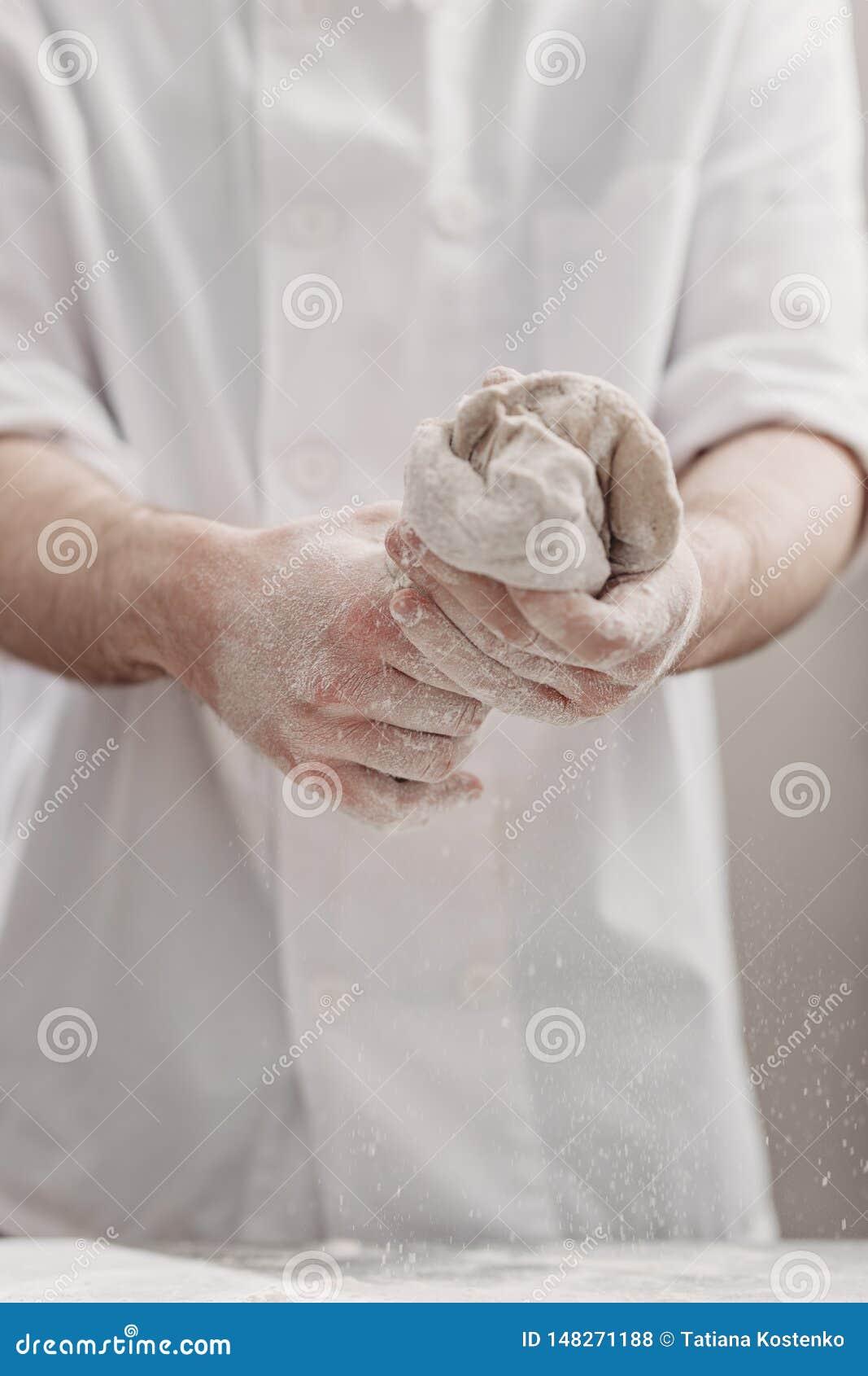 El panadero profesional amasa la pasta en sus manos en la cocina de la panader?a