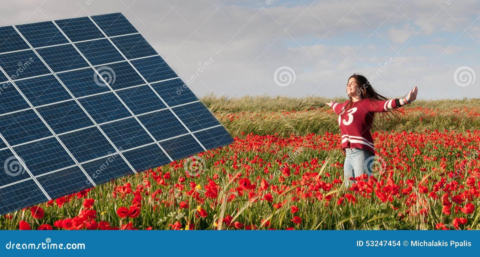 El panel y adolescente de energía solar en un campo con las amapolas rojas