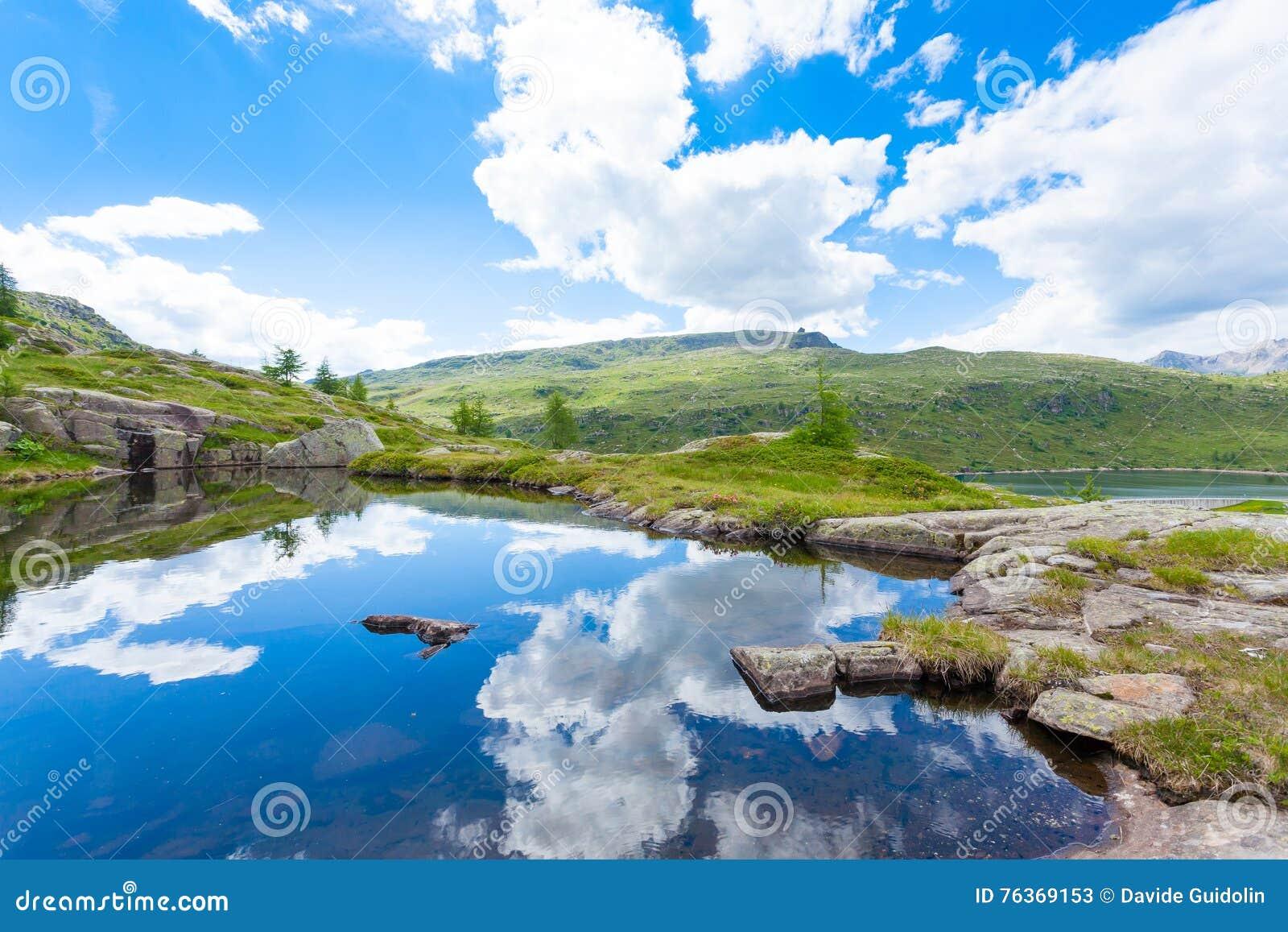 El panorama italiano de la montaña, nubes reflejó en el lago alpino