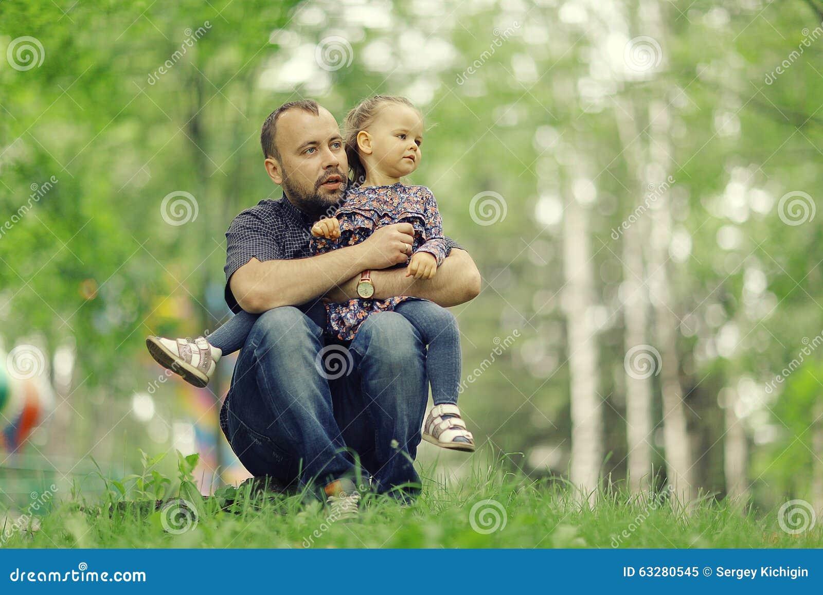 El papá camina con su hija en parque