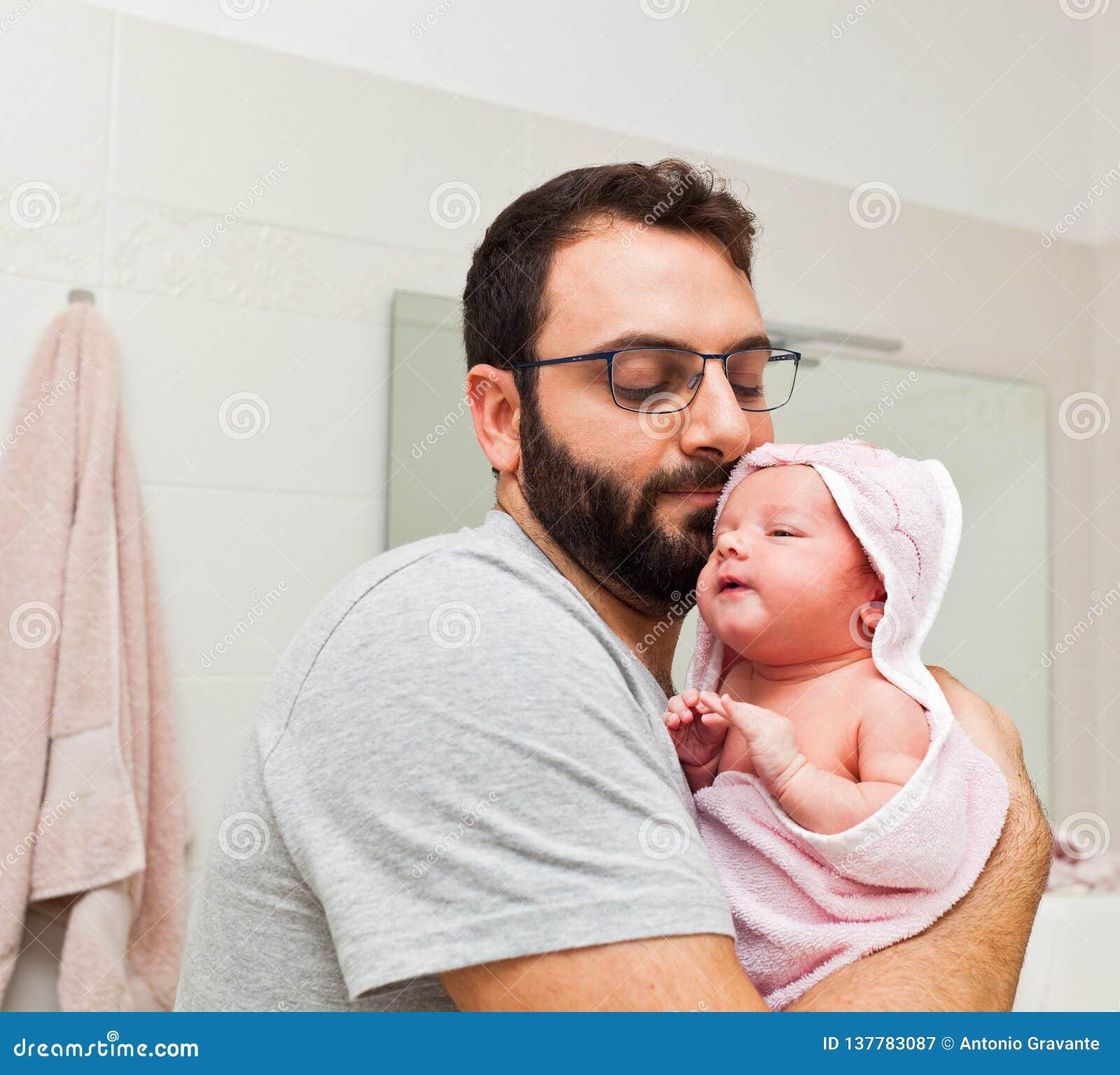 El papá detiene a su hija en sus brazos después del primer baño