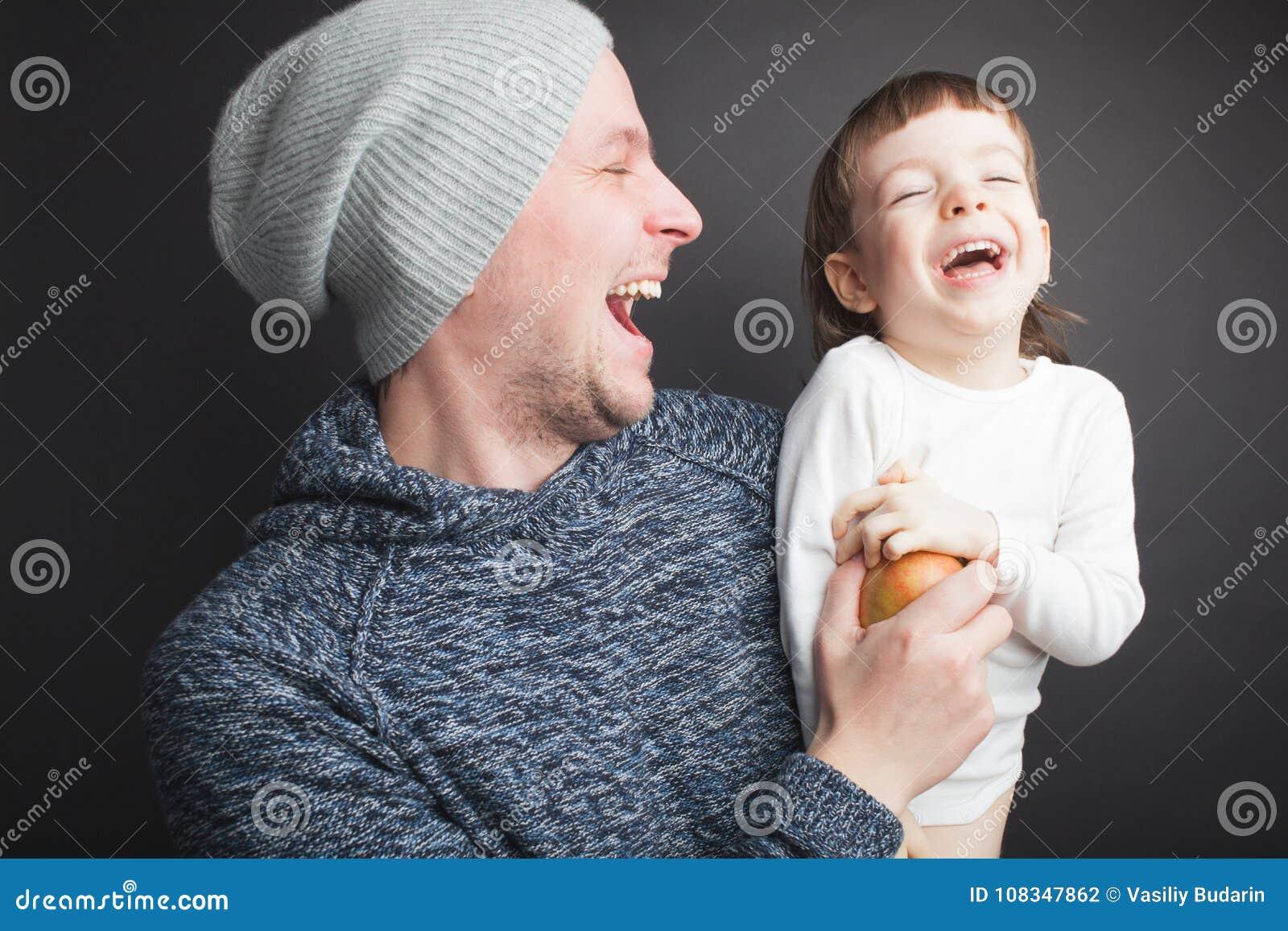 El papá juega con un pequeño hijo precioso, sentándose en sus manos en un fondo negro en el estudio Lo divierte con Apple y ellos