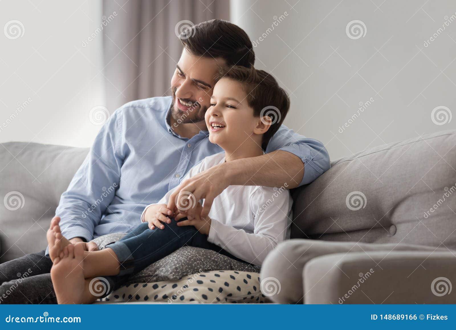 El pap? y el hijo sonrientes relajan el abrazo en el sof? en casa