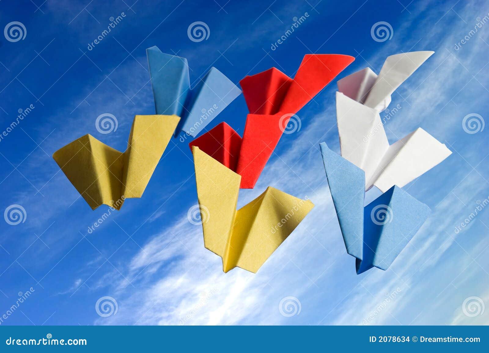 El papel abstracto del origame acepilla en fondo del cielo nublado
