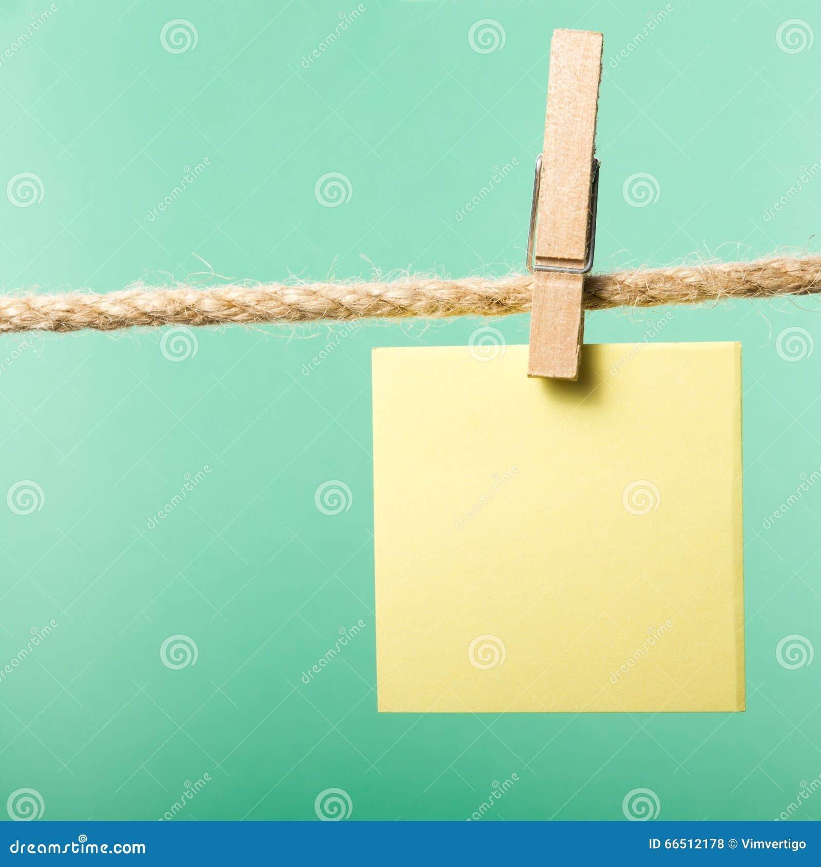 El papel en blanco observa la ejecución en la cuerda con los pernos de ropa, espacio de la copia