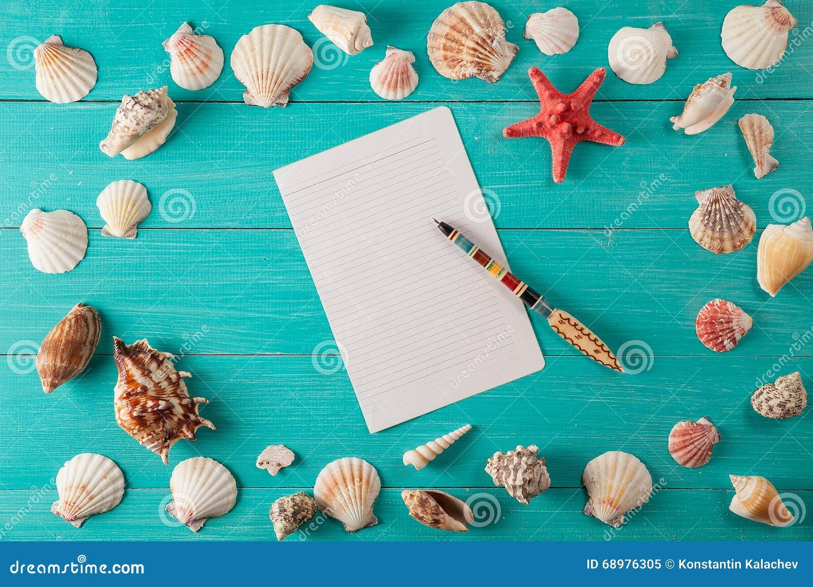 El papel para las notas acerca a conchas marinas en fondo de madera Copie el espacio