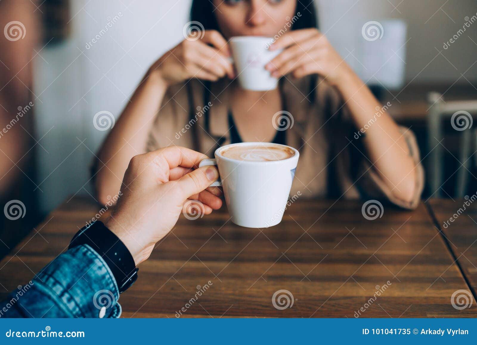 El par bebe el café de la mañana en café