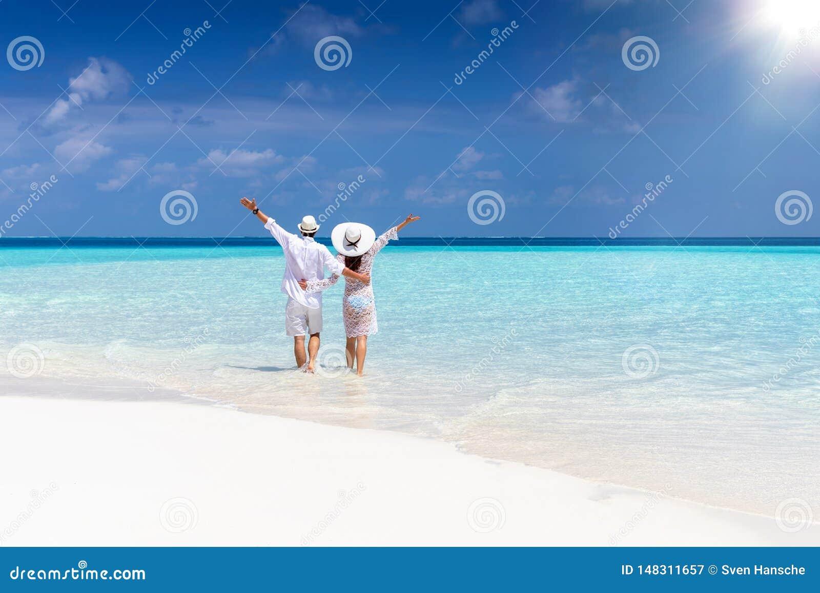 El par camina abajo de una playa tropical en la ropa blanca
