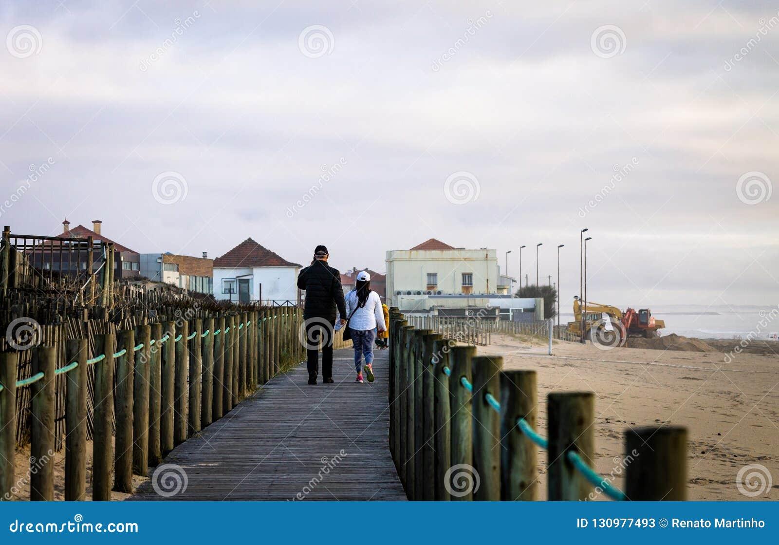 El par camina en paseo marítimo en la playa