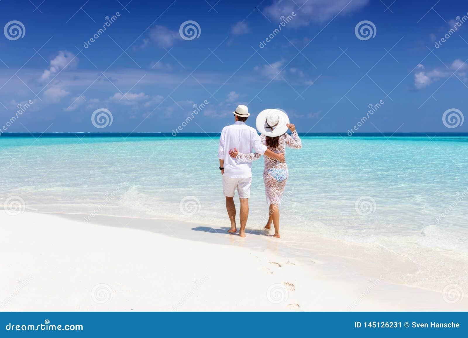 El par camina a lo largo de una playa tropical en los Maldivas
