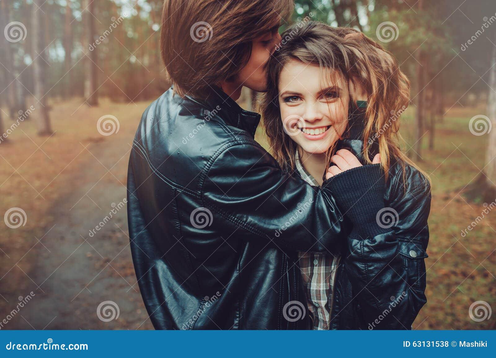 El par cariñoso feliz joven en las chaquetas de cuero abraza al aire libre en paseo acogedor en bosque