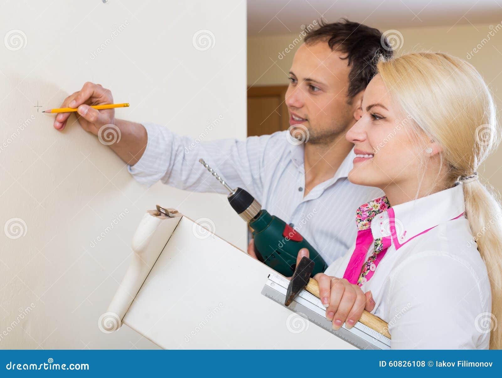 El par cuelga el estante en una pared