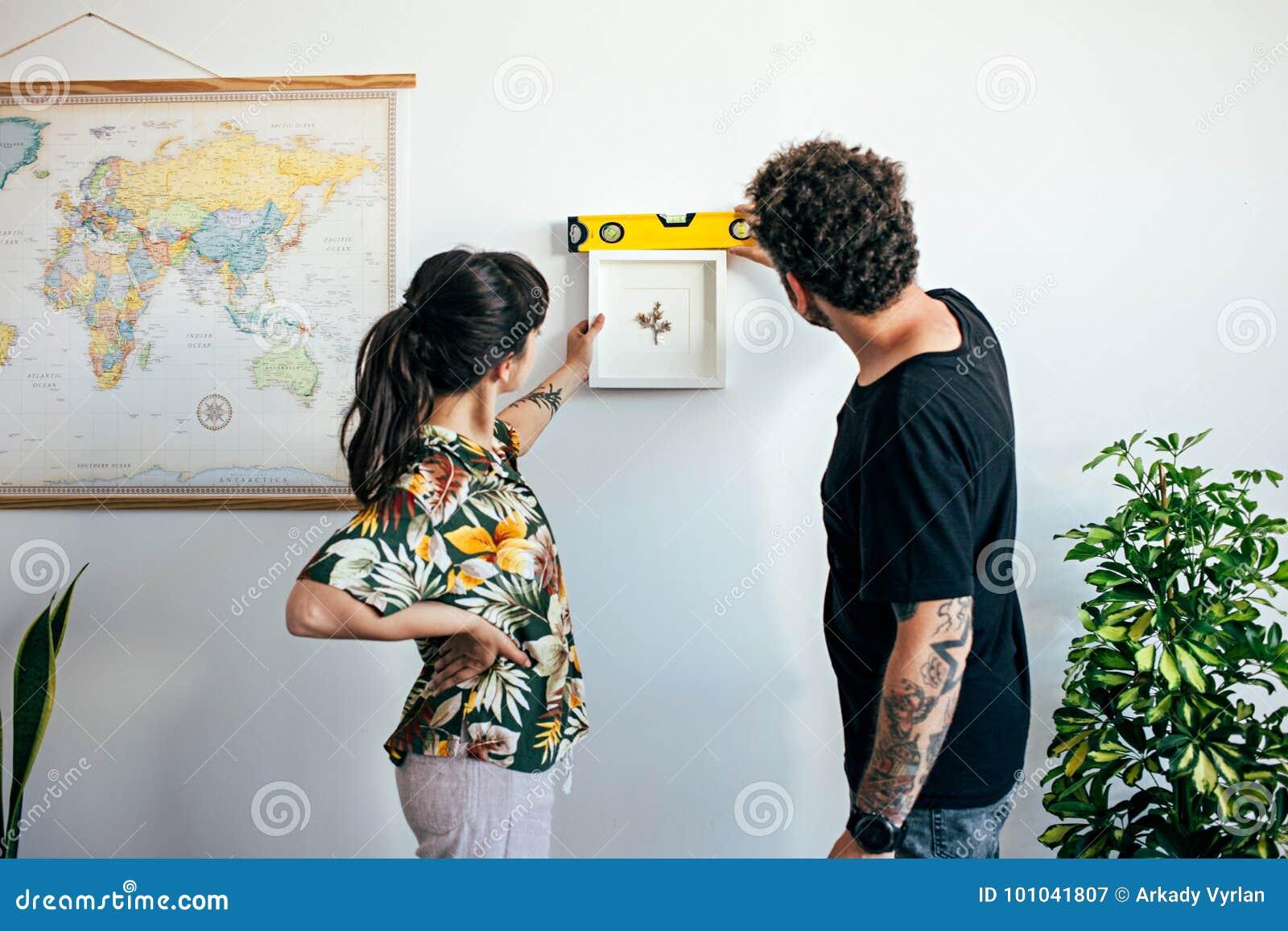 El par cuelga la pintura del marco en la pared