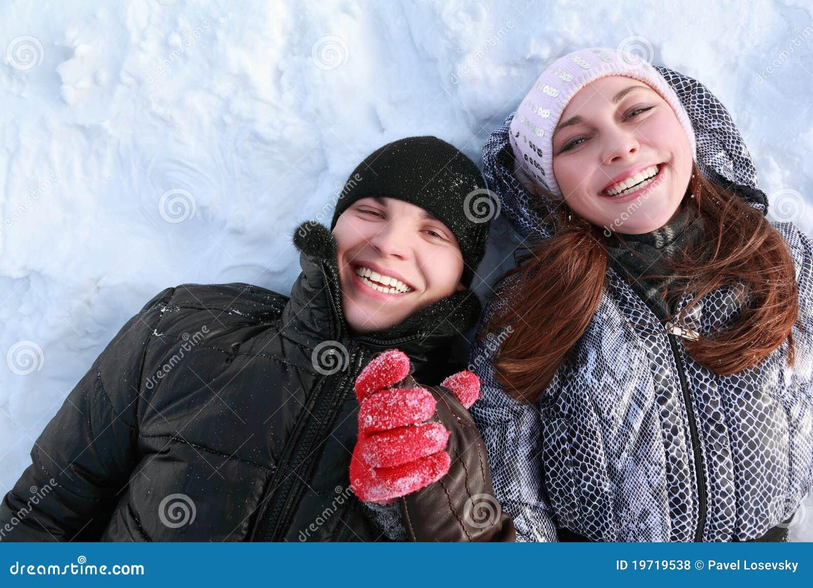 El par de gente de los amantes miente en nieve y risa