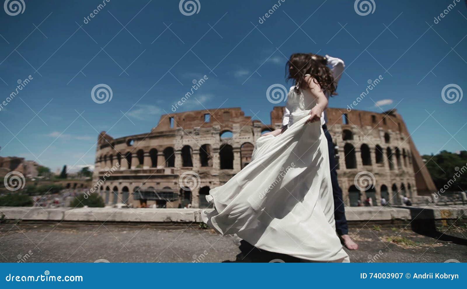 El Par De La Boda En Roma Por Coliseo, Novio Feliz Mira Su Baile De ...