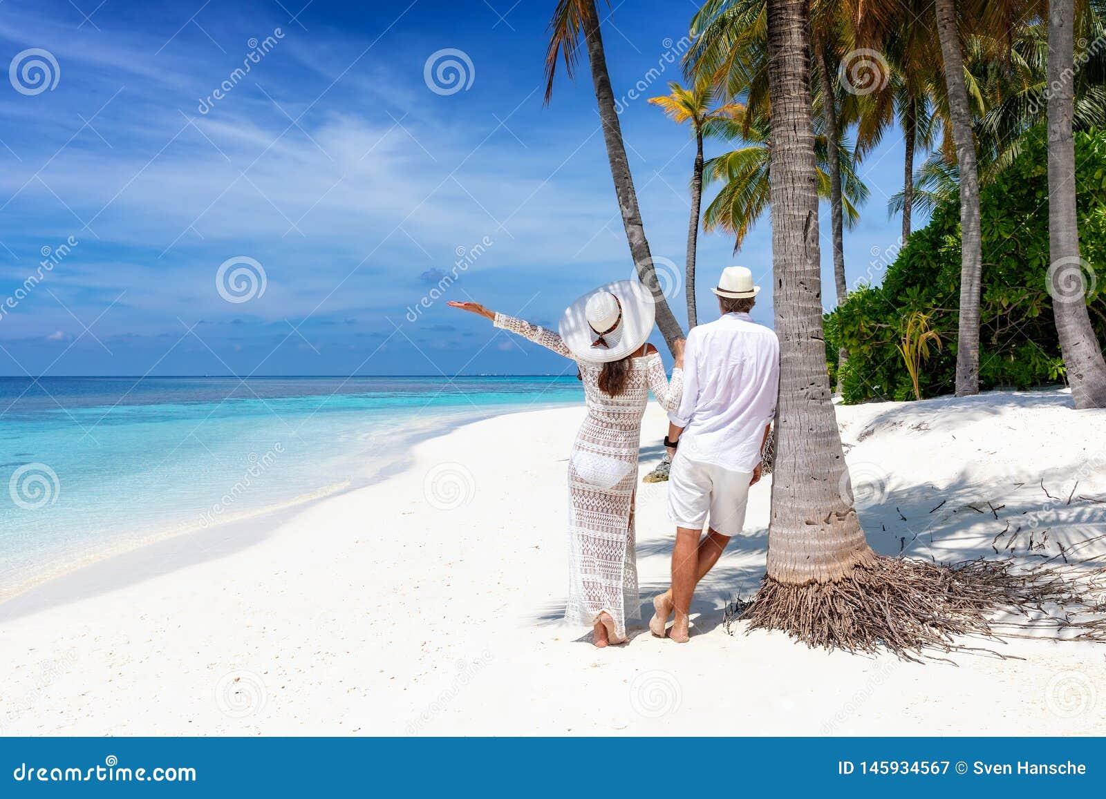 El par del viajero se coloca en una playa hermosa, tropical