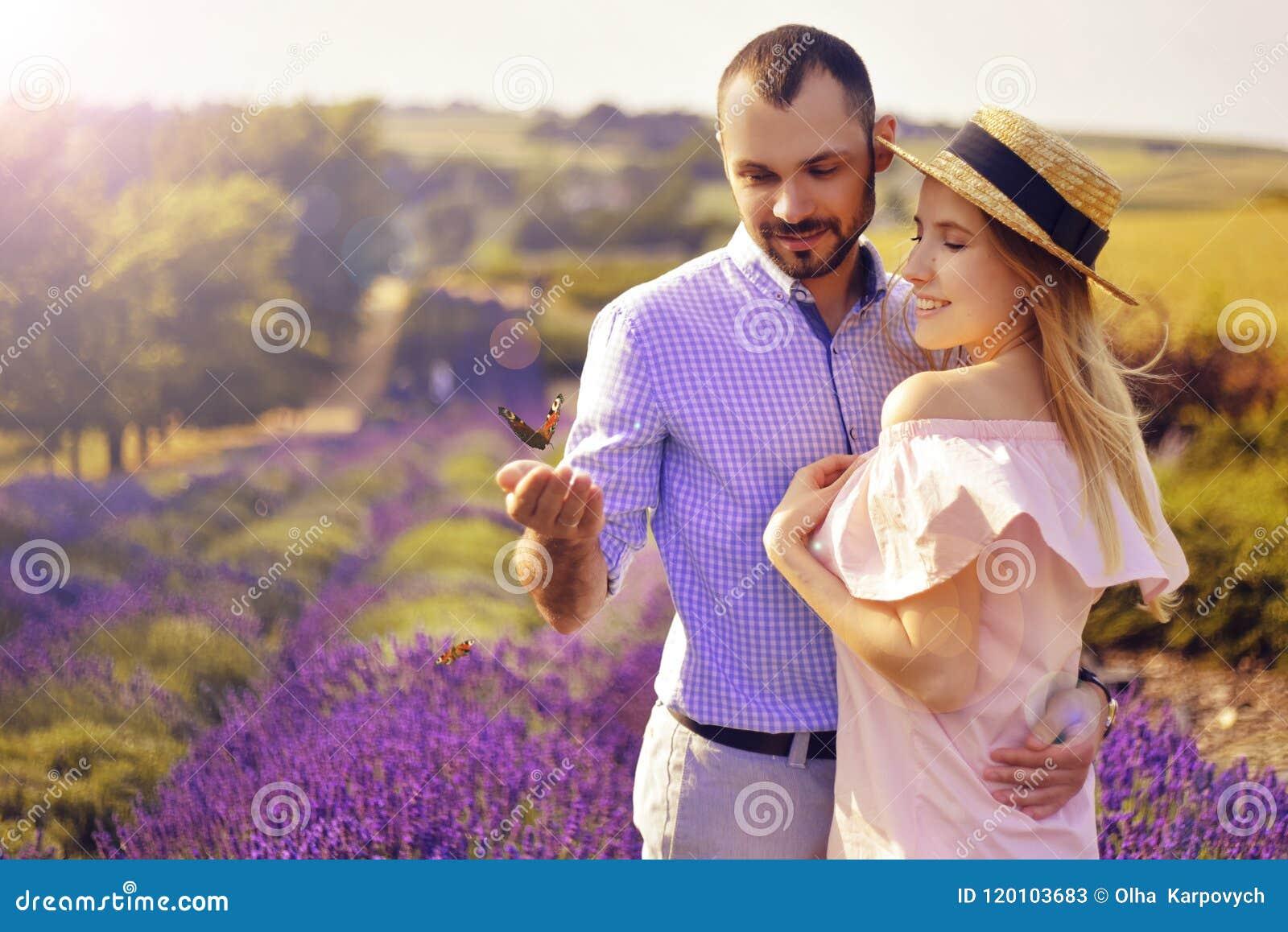 El par feliz joven lindo en amor en un campo de la lavanda florece Disfrute de un momento de felicidad y de amor en un campo de l