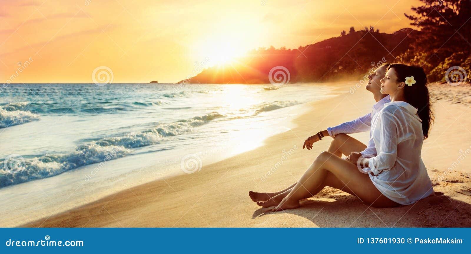 El par feliz se sienta en la costa del océano