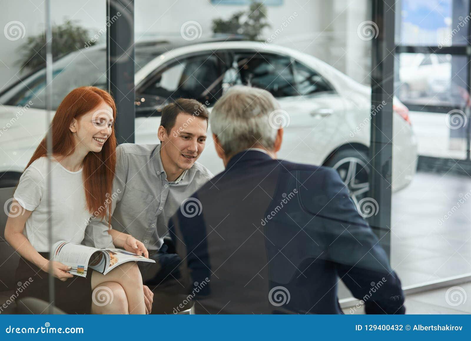 El par hermoso feliz está comprando un nuevo coche en la representación Consejo de la familia