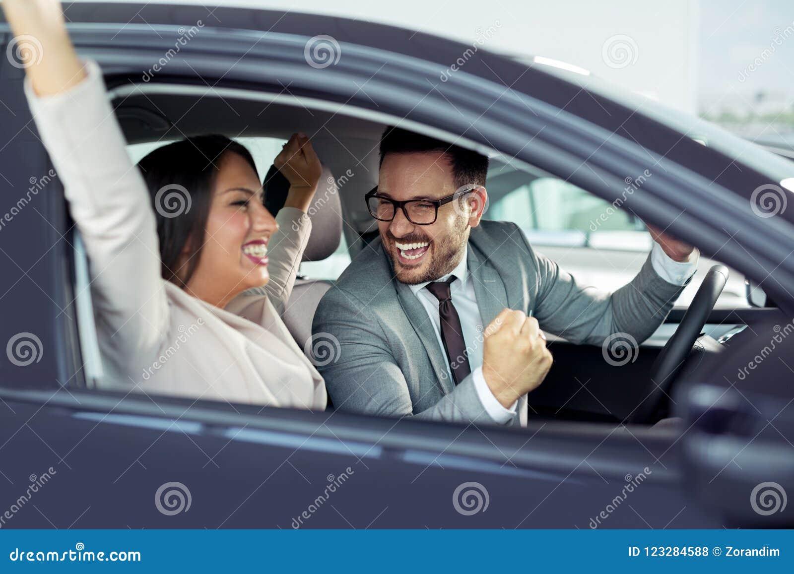 El par hermoso feliz está eligiendo un nuevo coche en la representación