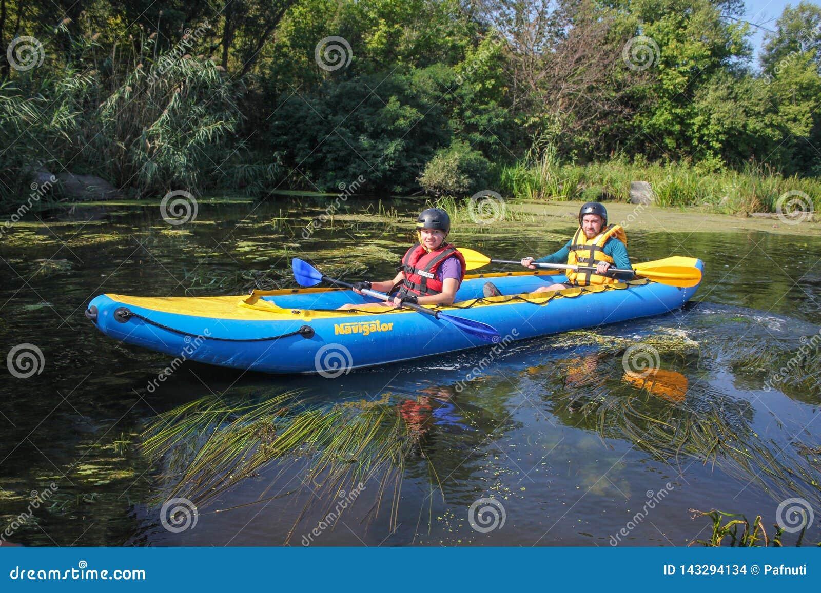 El par joven feliz en chalecos de vida está sonriendo mientras que navega un kajak