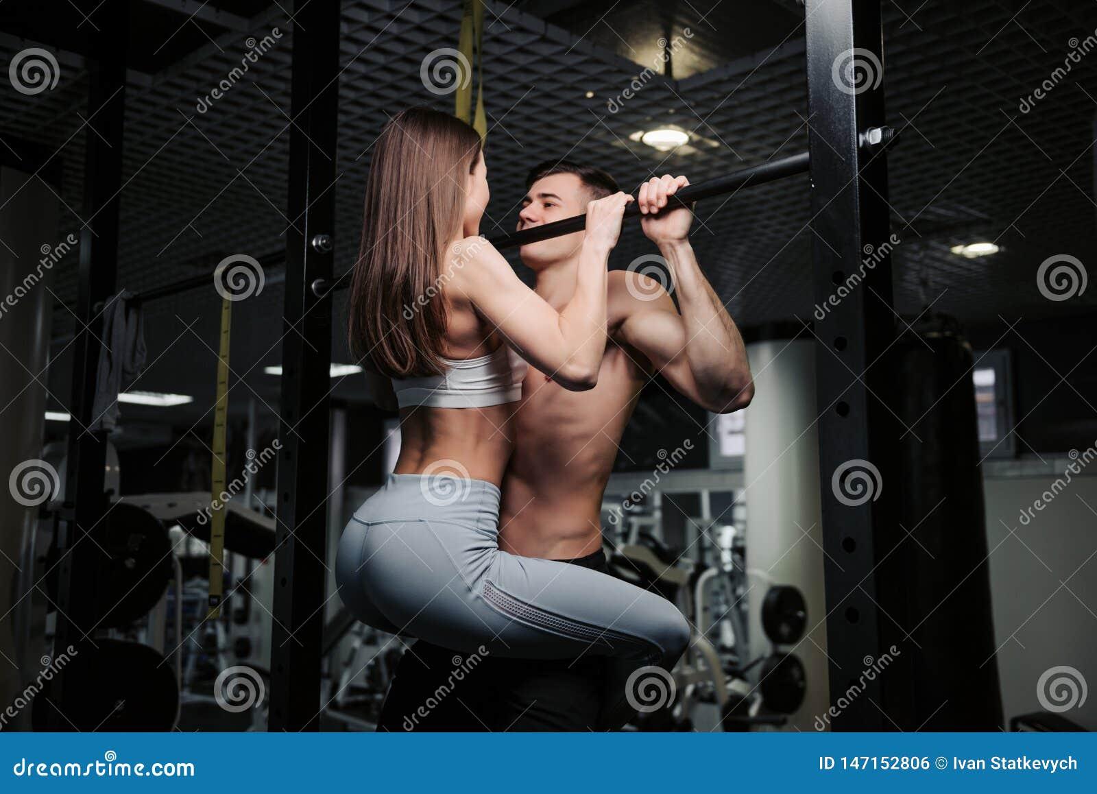 El par joven se est? resolviendo en el gimnasio La mujer atractiva y el hombre muscular hermoso est?n entrenando en gimnasio mode