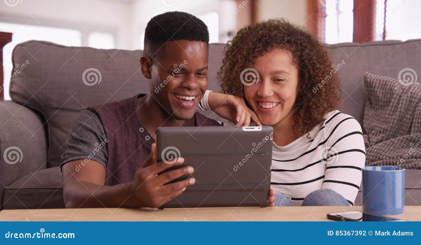 El par negro milenario auténtico se sienta en el piso que mira un vídeo en su tableta