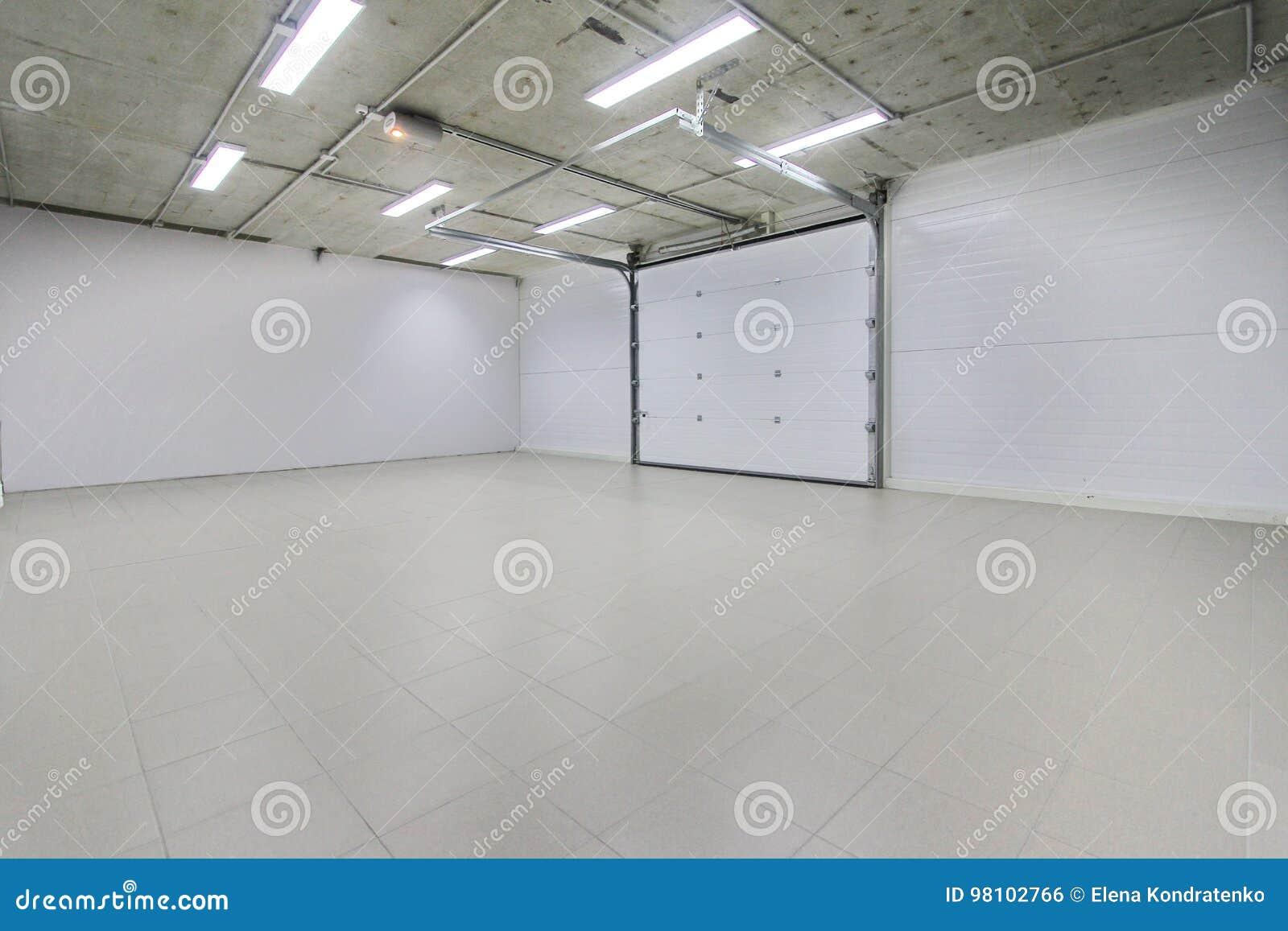 El parking vacío, almacena el interior con las puertas blancas grandes y el suelo de baldosas gris