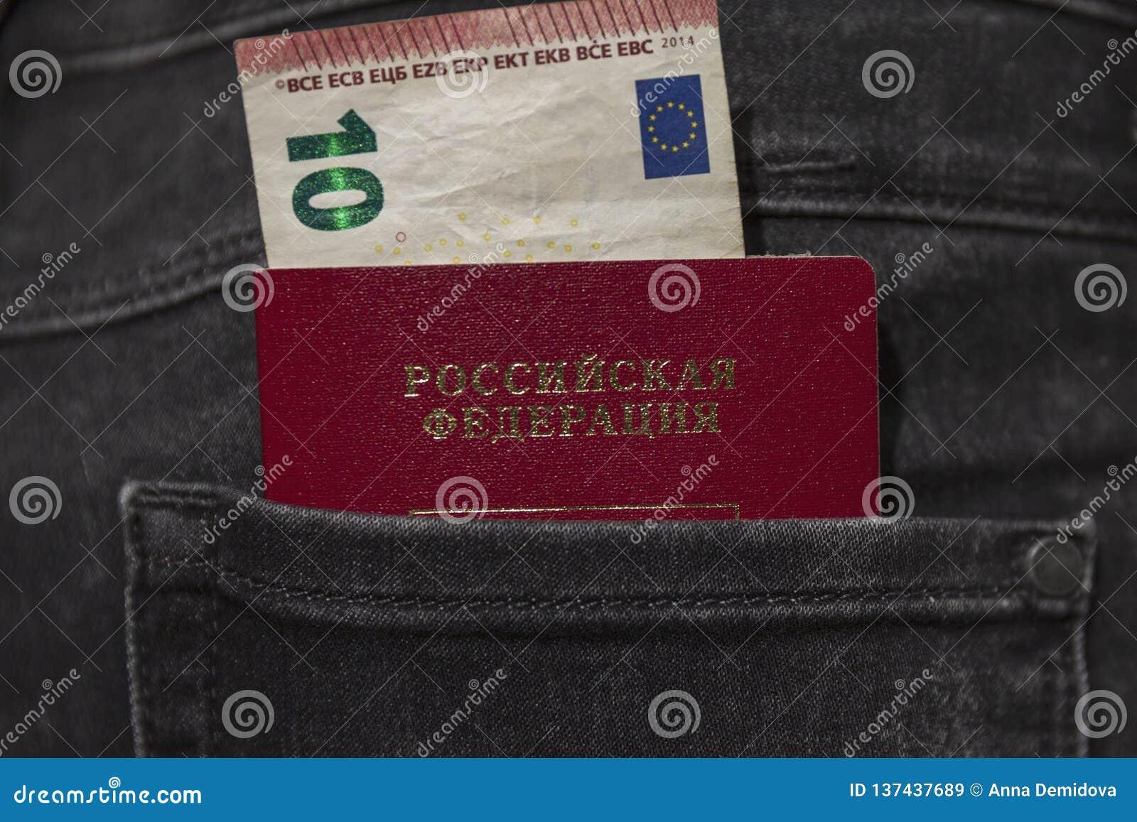 El pasaporte ruso y una cuenta de 10 euros se pegan fuera del bolsillo trasero de vaqueros