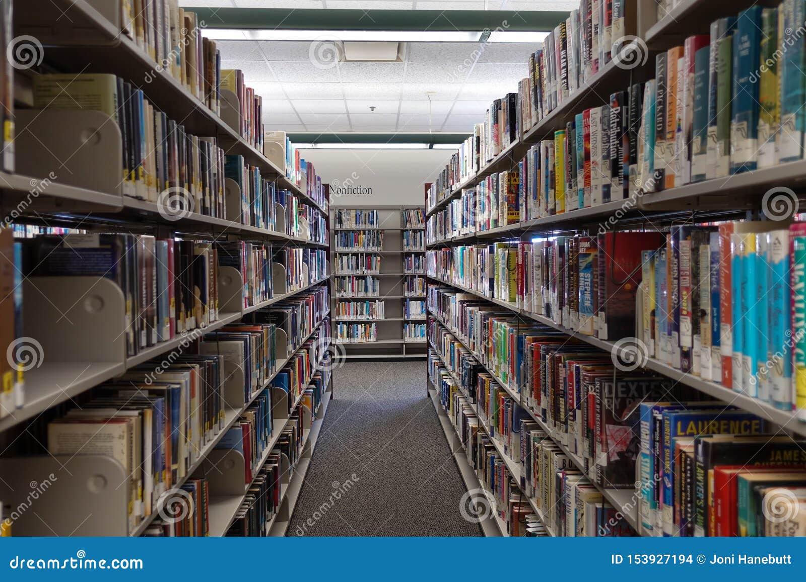 El pasillo de la ficción de una biblioteca pública que muestra filas de libros