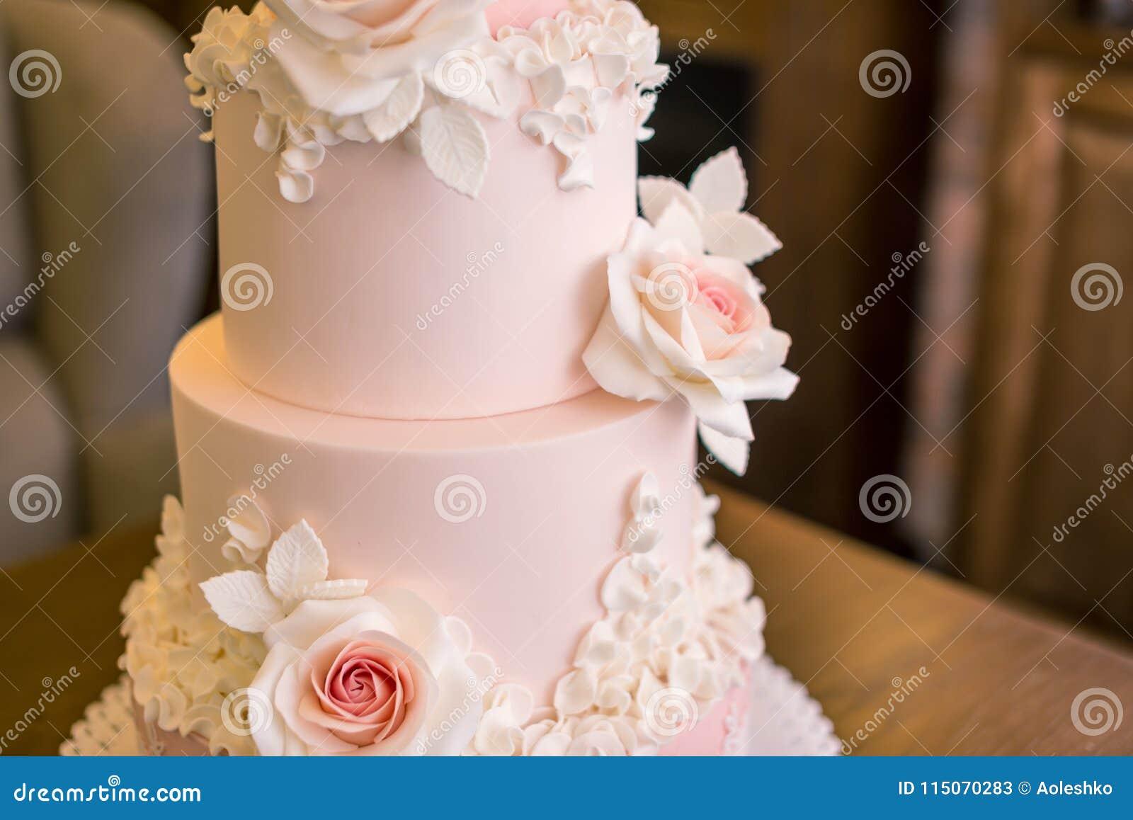El pastel de bodas rosado con gradas cuatro elegantes hermosos adornado con las rosas florece Concepto floral de la masilla del a