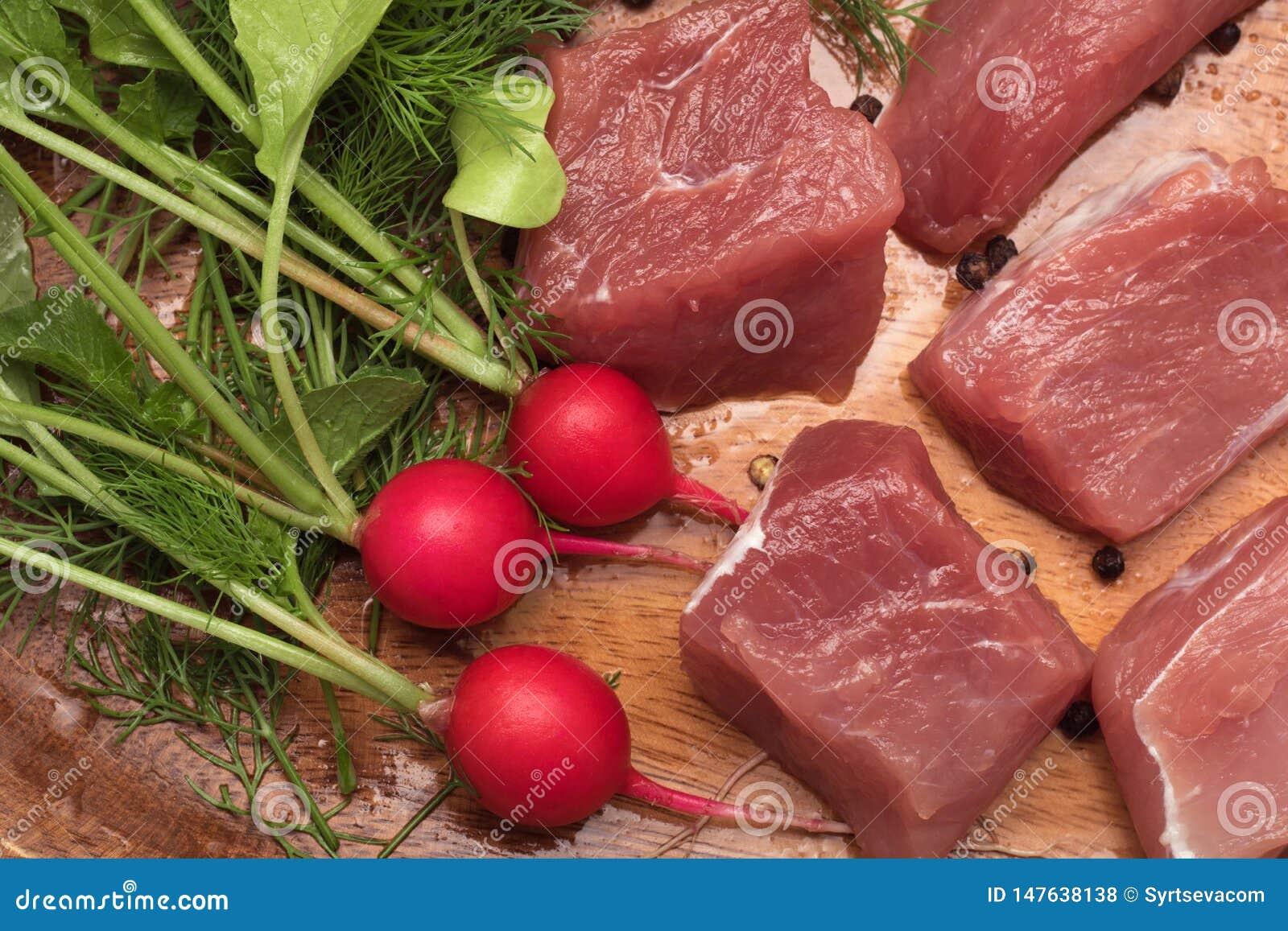 El pedazo de carne jugoso sirvi? en una placa de madera con el condimento, las hierbas y las verduras