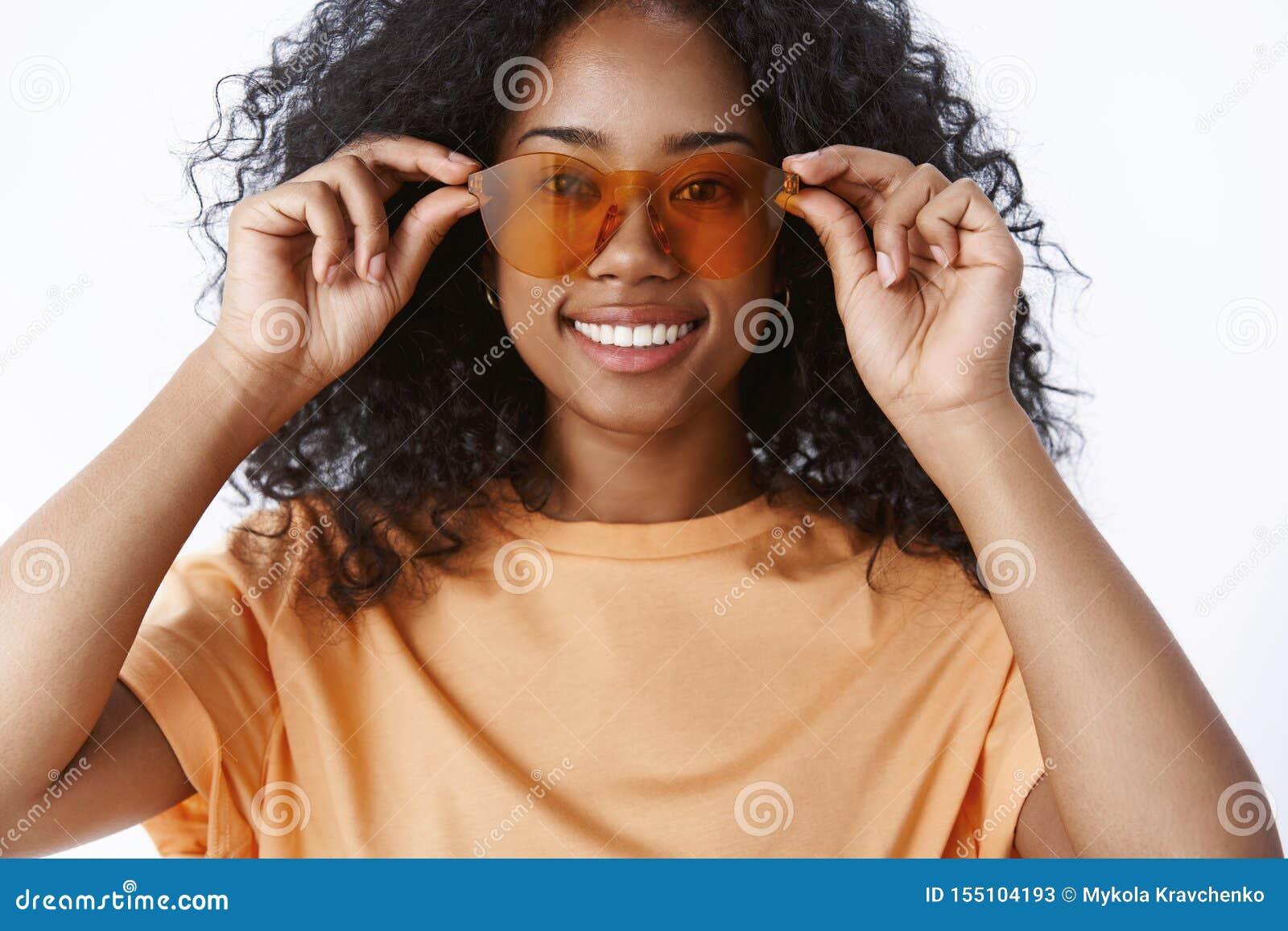 El peinado afro sonriente encantador de la muchacha afroamericana del primer que comprueba las gafas de sol bying los nuevos vidr