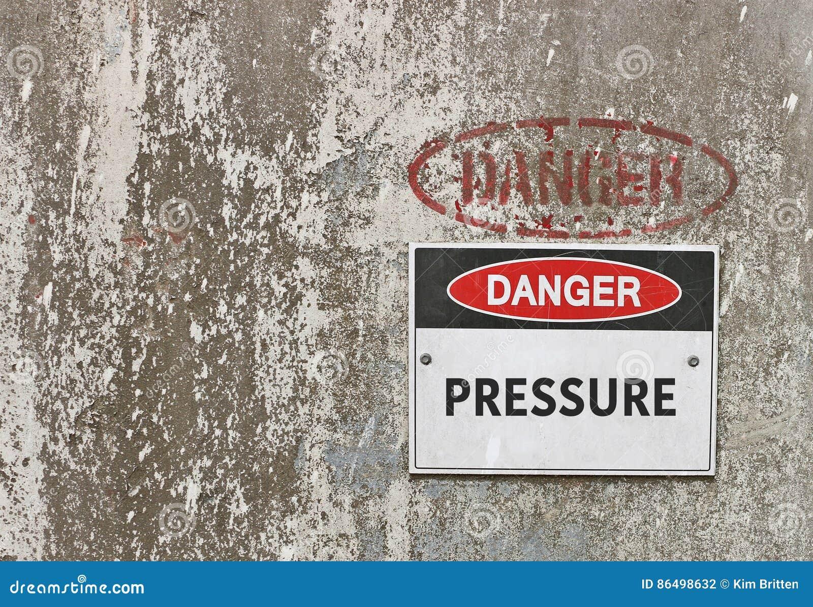 El peligro rojo, blanco y negro, ejerce presión sobre la señal de peligro