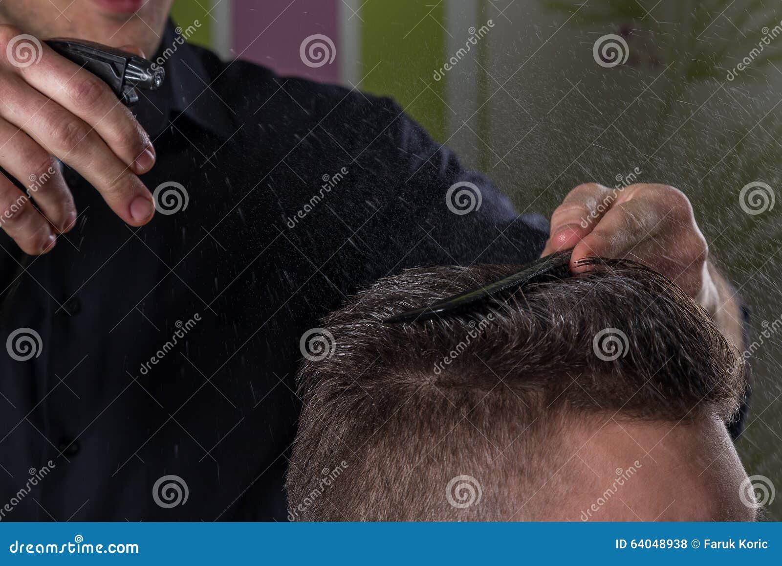 El peluquero hace el pelo con agua y el peine del cliente en salón profesional de la peluquería
