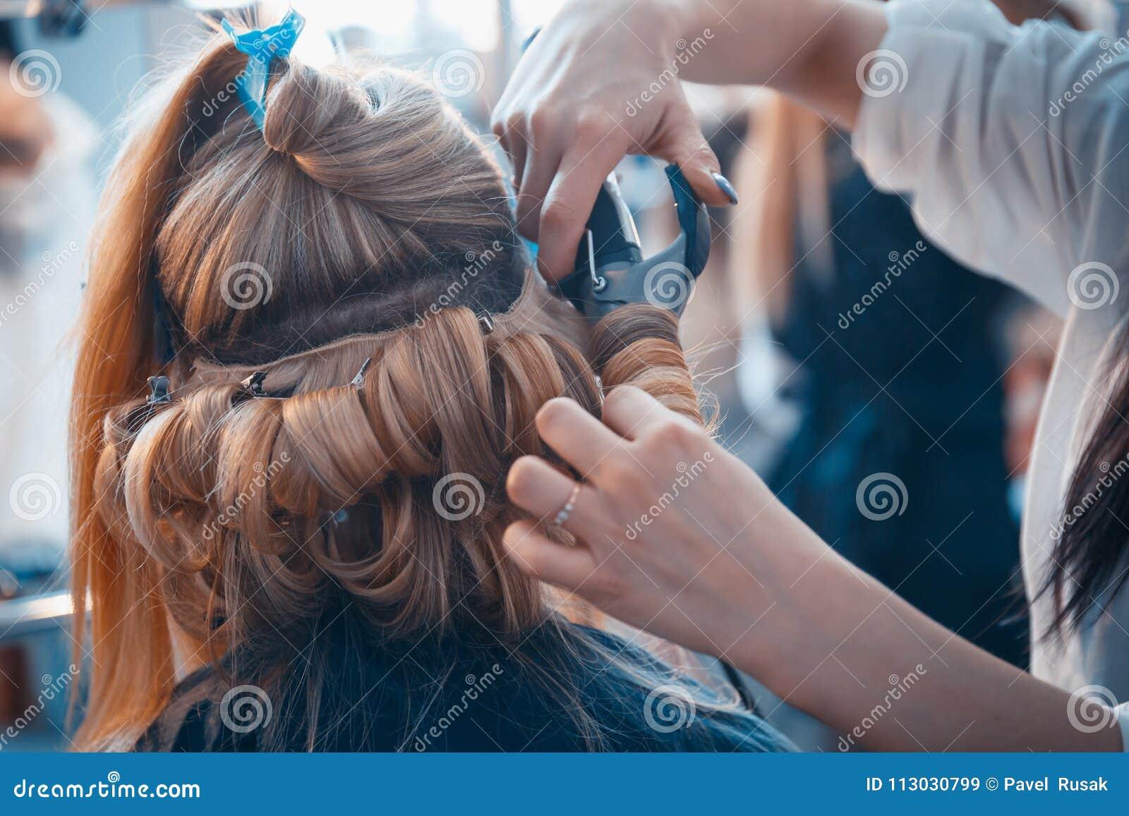 El peluquero hace extensiones del pelo a una chica joven