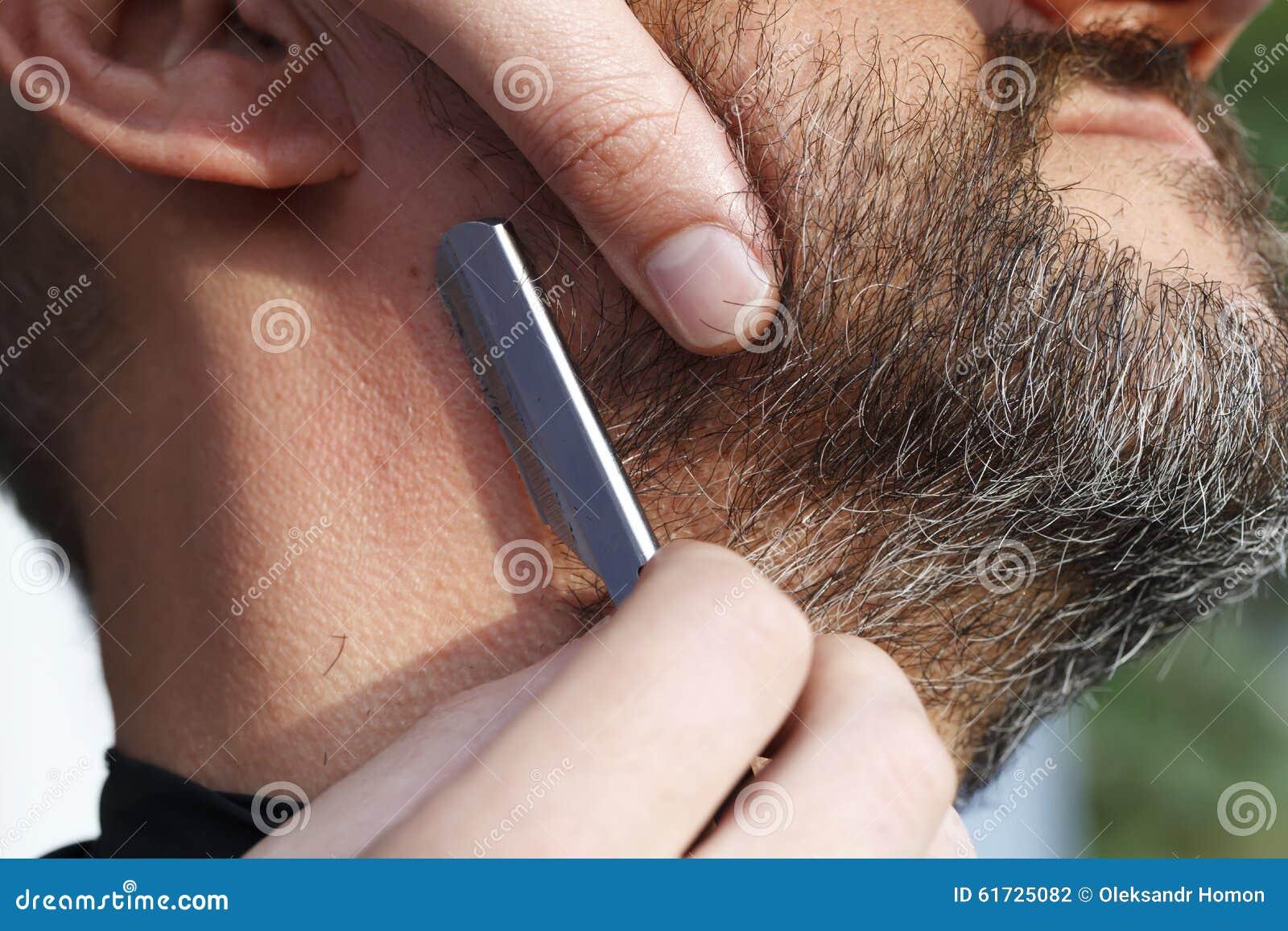 El peluquero principal esquila al hombre de la barba