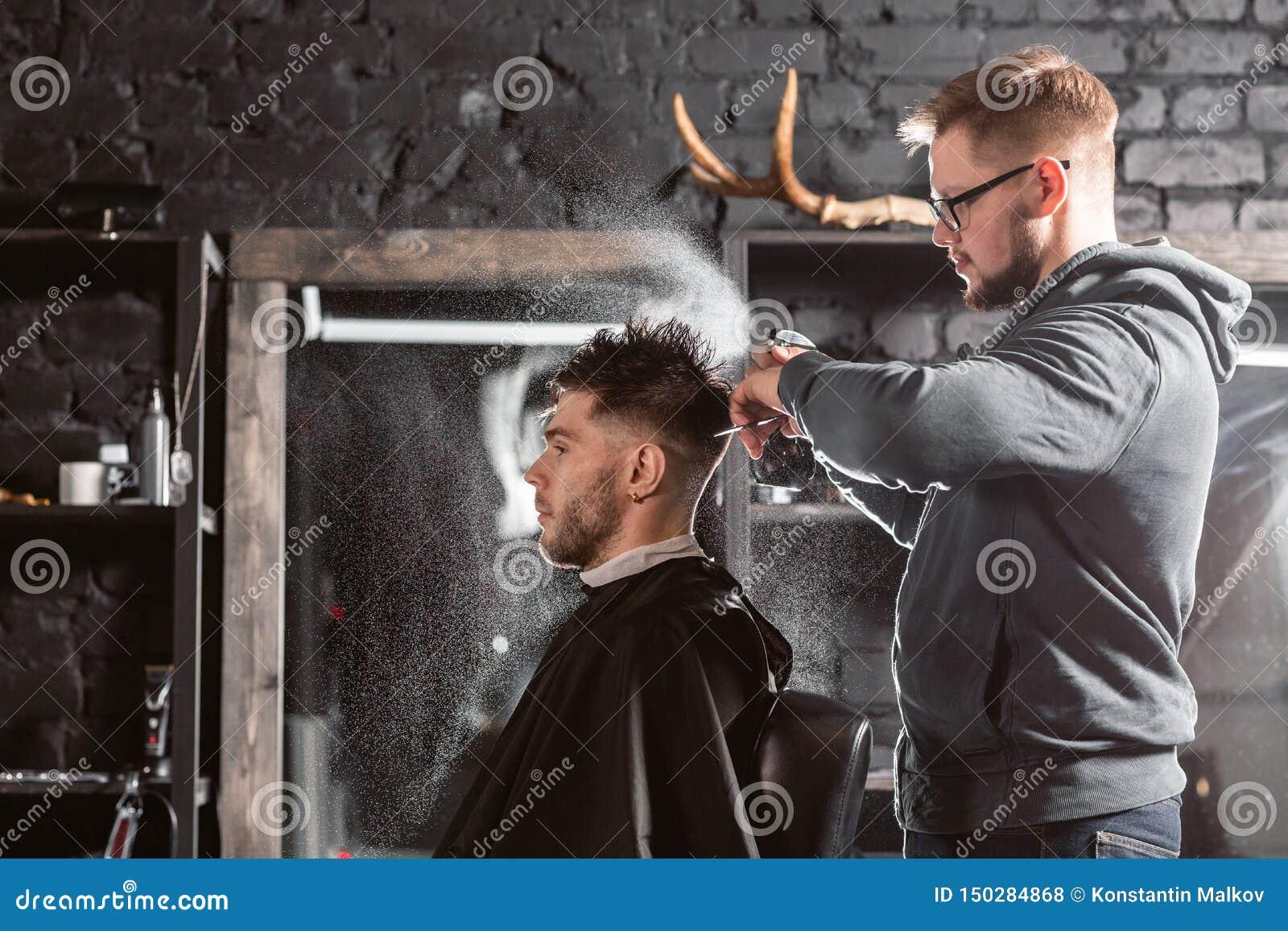 El peluquero roc?a el agua potable en la cabeza en barber?a La herramienta profesional del condensador de ajuste corta la barba y