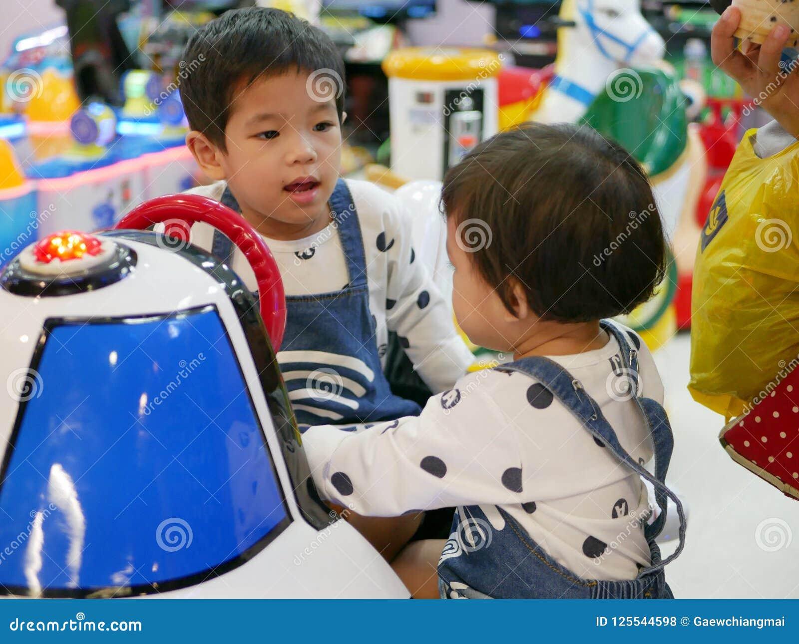 El pequeño bebé asiático rechaza dejar a su hermana del bebé jugar a un juego de arcada junto