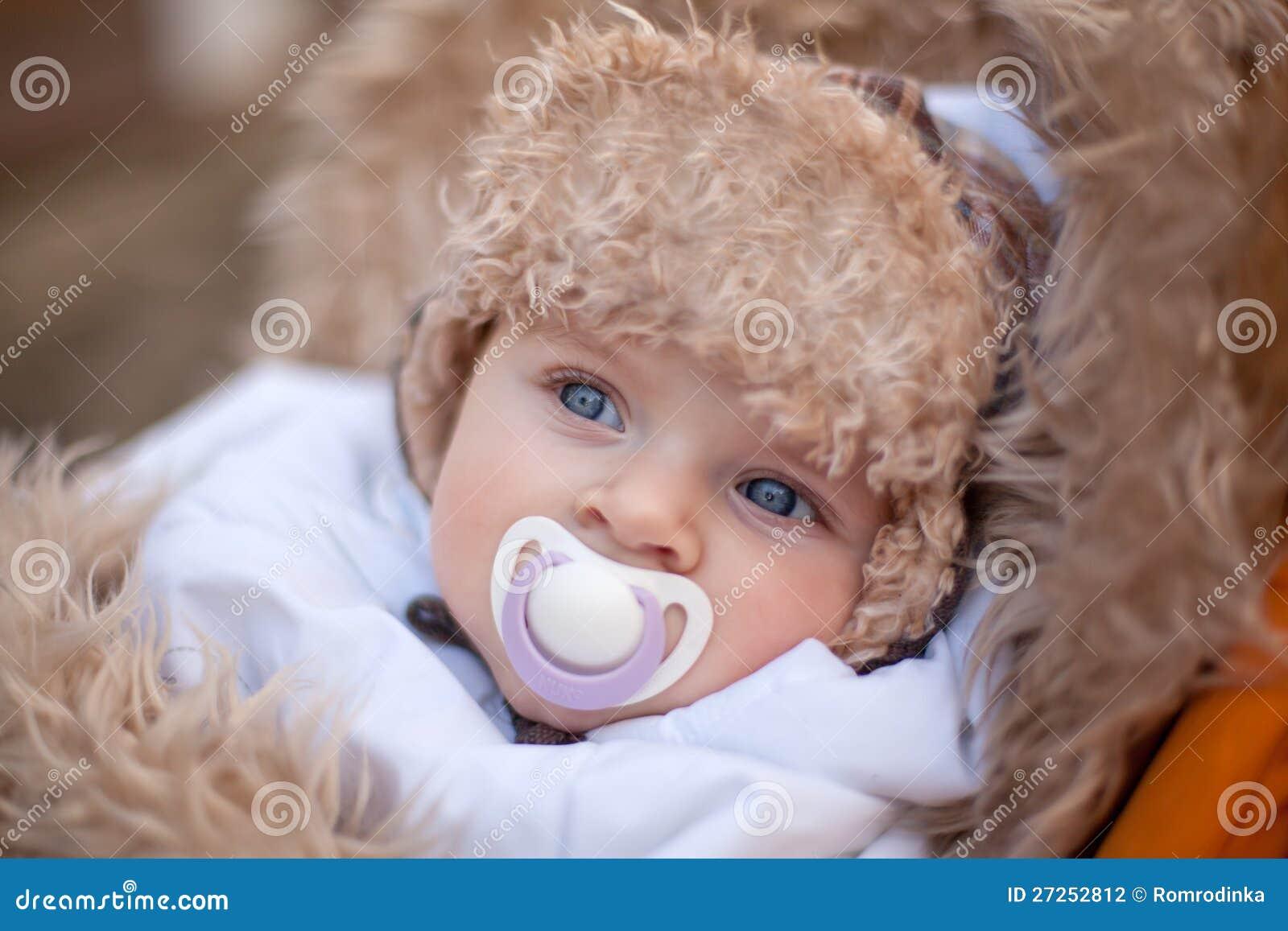 El pequeño bebé en invierno caliente arropa al aire libre
