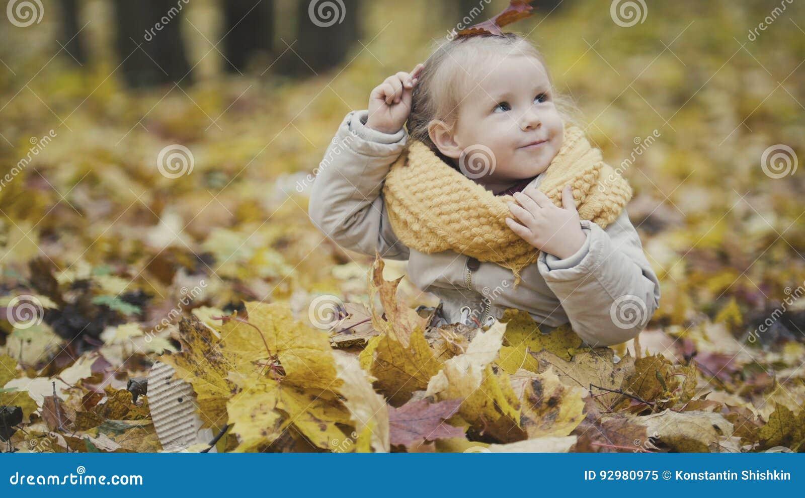 El pequeño bebé feliz juega en parque del otoño entre las hojas amarillas