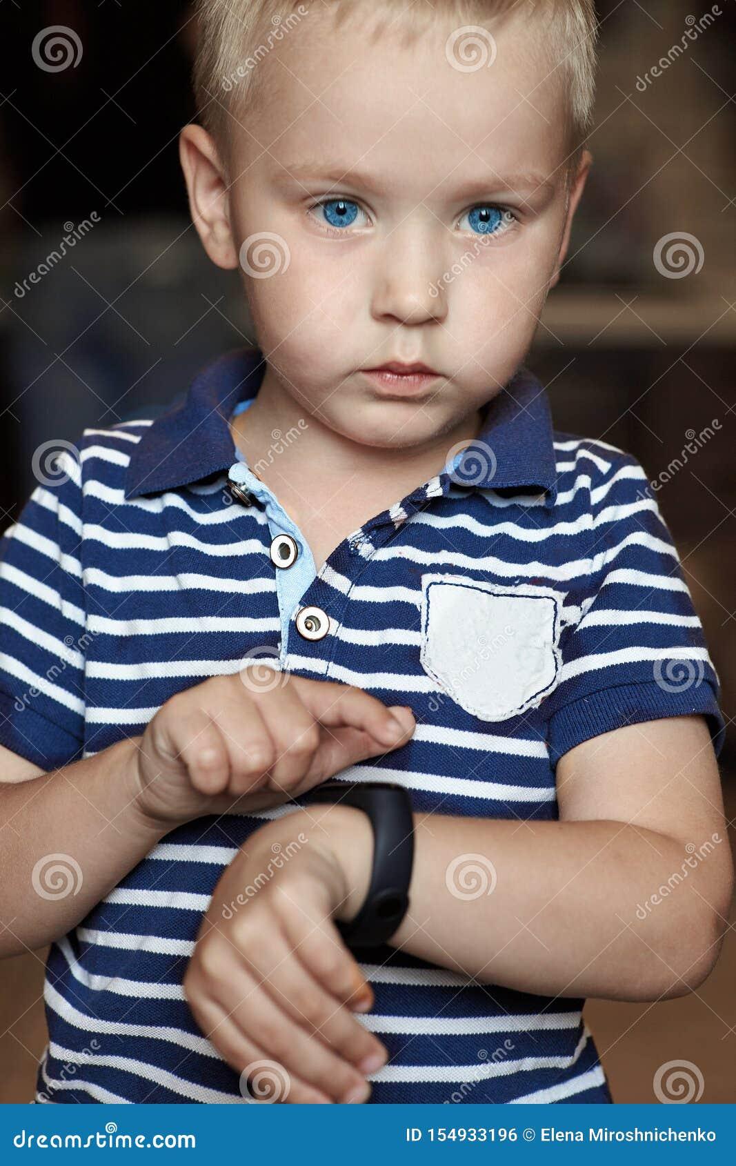 El pequeño muchacho rubio lindo con los ojos azules señala al perseguidor digital de la aptitud en su muñeca