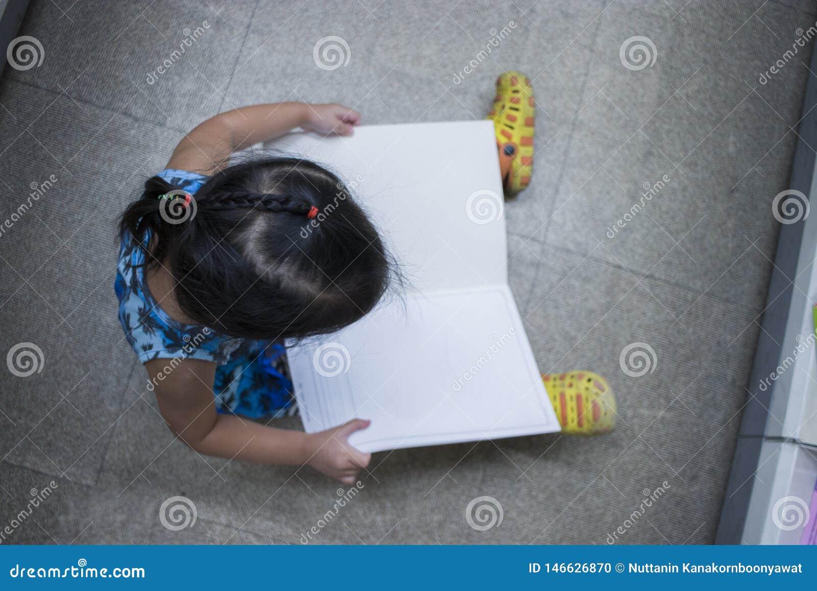 El pequeño niño explora y leyendo un libro en la opinión superior de la librería
