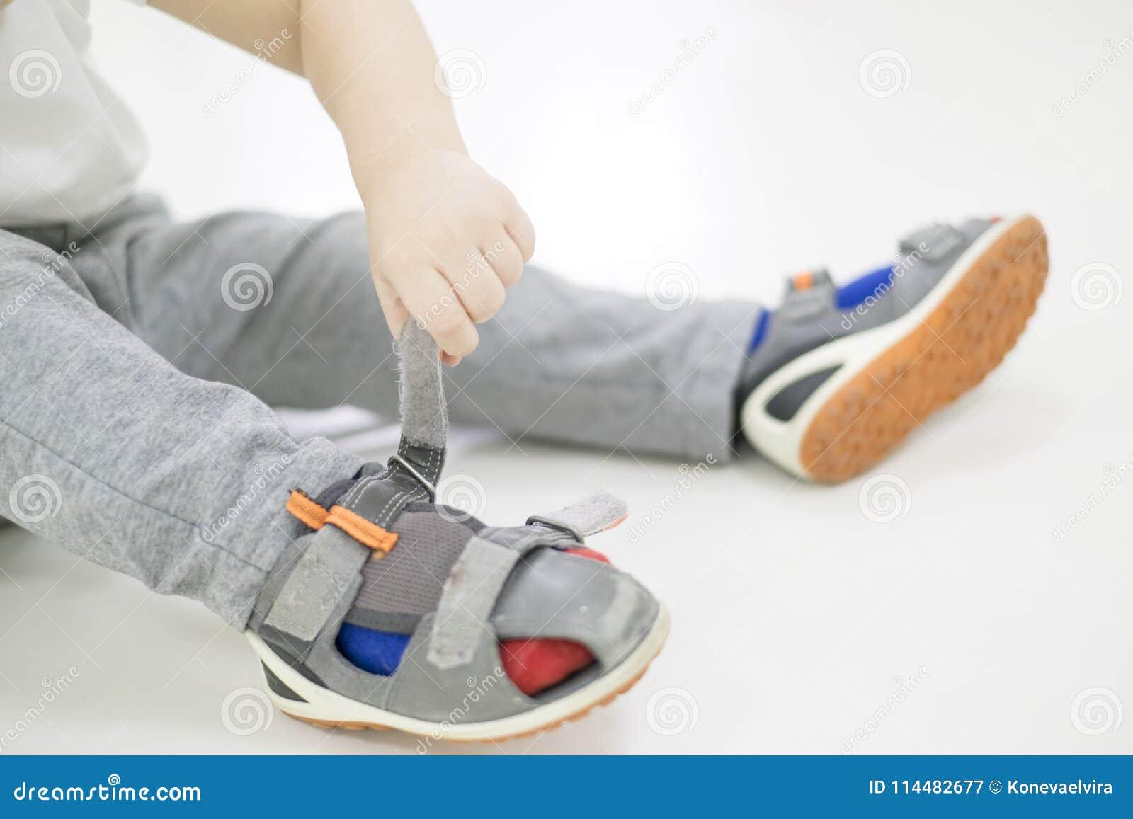 cfa50609 El pequeño niño intenta poner sus zapatos Bebé con los zapatos a  disposición cómo elegir los