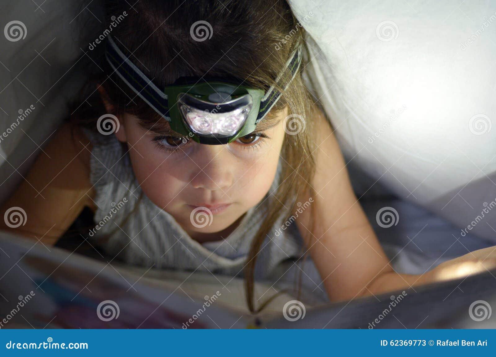 El pequeño niño leyó el libro en cama bajo cubiertas en la noche
