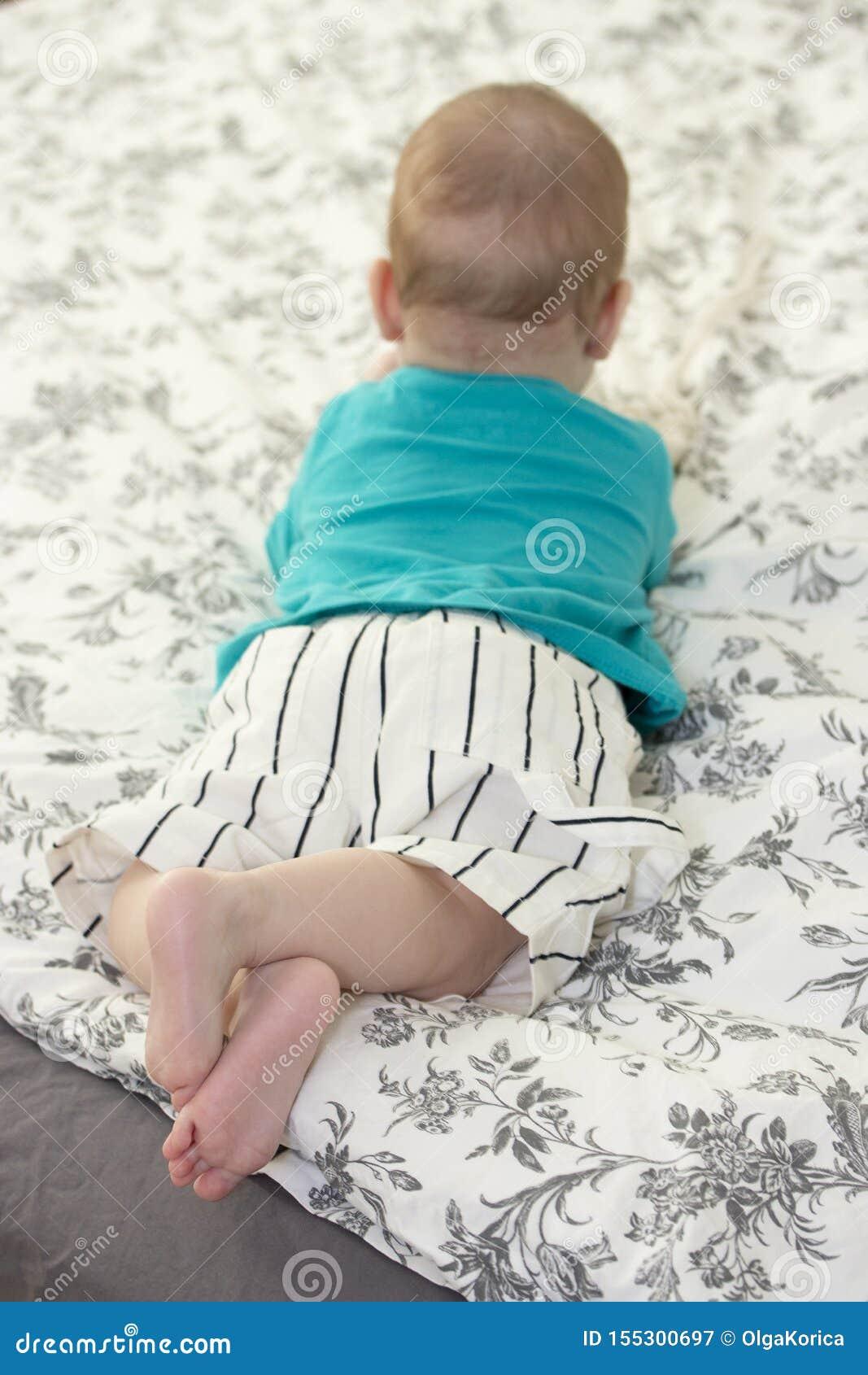 El pequeño niño miente en la cama, visión desde la parte posterior Muchacha del bebé que descansa con los pies desnudos cruzados