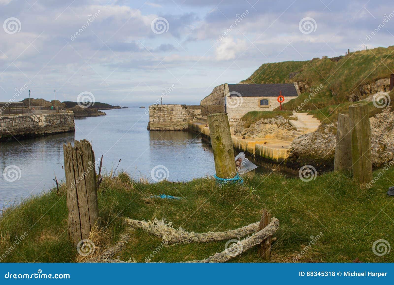 El pequeño puerto en Ballintoy en la costa del norte de Antrim de Irlanda del Norte con su varadero construido de piedra en un dí