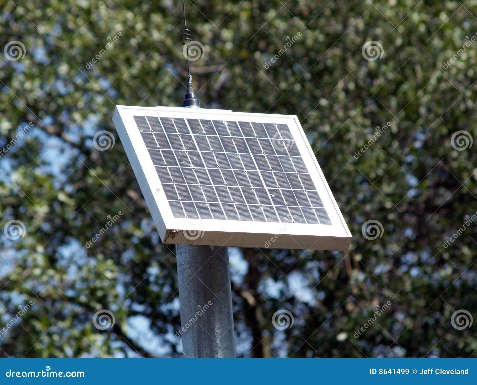 El peque o panel solar en poste con los rboles im genes for Panel solar pequeno