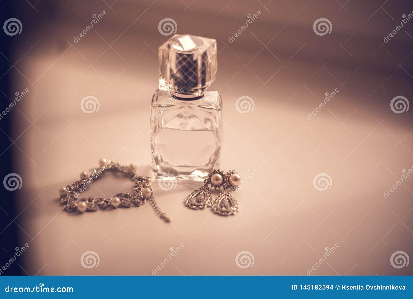 El perfume de la novia, pendientes, collar, anillos de las joyas y liga determinados del cordón que se casan en la tabla de made