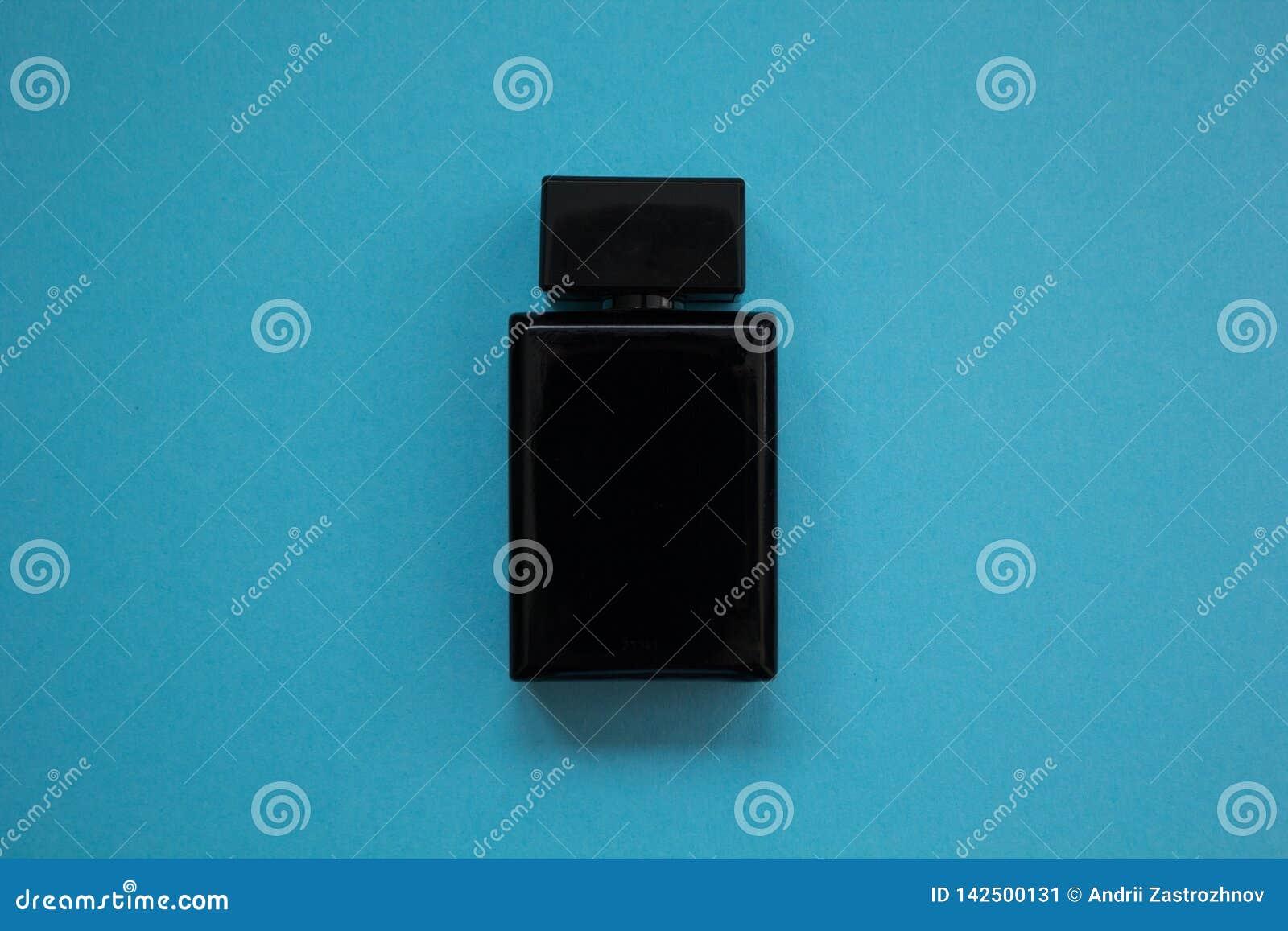 El perfume de los hombres en botella negra hermosa en un fondo azul